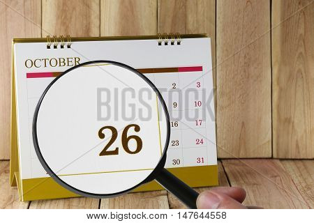 Magnifying glass in hand on calendar you can look Twenty-six date of monthFocus number Twenty-six in OctoberConcept in business and meetings.