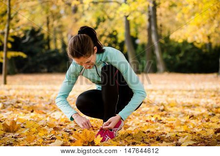 Young woman jogging tying shoelaces on jog in autumn nature