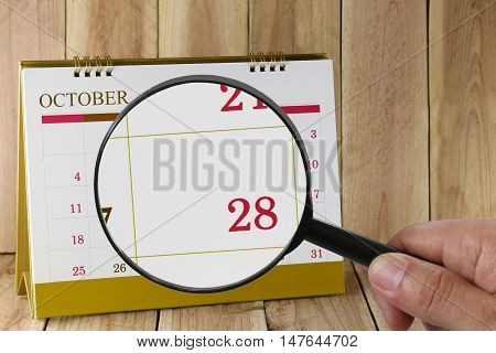 Magnifying glass in hand on calendar you can look Twenty-eight date of monthFocus number Twenty-eight in OctoberConcept in business and meetings.