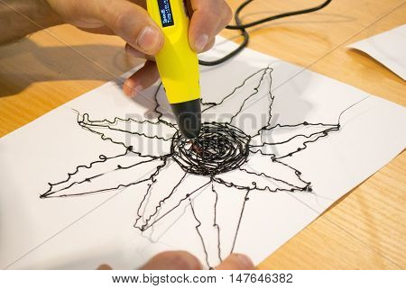 Man 3d pen draws a flower on white paper close-up,