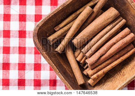 Cinnamon stick in bowl on checkered tablecloth. Top view.