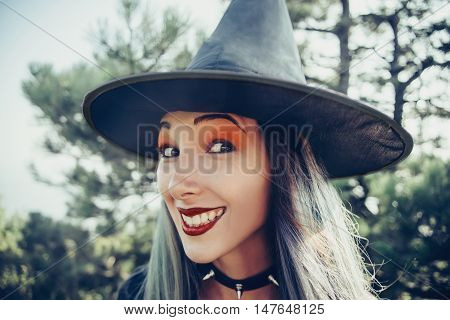 Portrait of cheerful witch. Young woman in costume of Halloween witch looking at camera