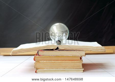 electric light bulb lying on an open book on the background of blackboard / bookmark creative idea