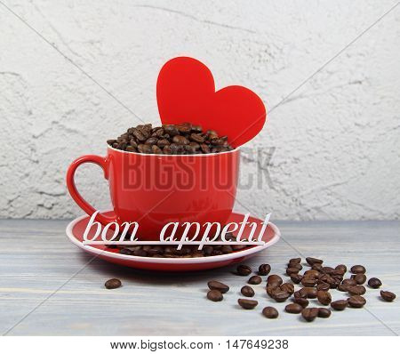 cup red with coffee grains, heart and an inscription bon appetit