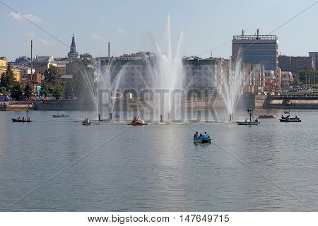 People ride on boats and catamarans in the city pond with fountain