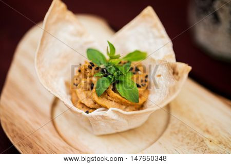 food, catering, cooking and eating concept - close up of dough cornet with filling