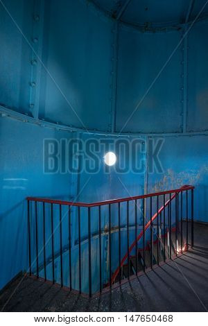 Old lighthouse on the inside. Red iron spiral stairs round window and blue wall. Kihnu small island in Estonia. Europe
