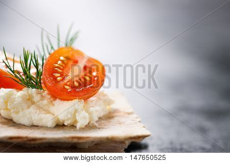 Appetizer canape with cherry tomato cheese and dill on a small loaf of bread closeup with place for text selective focus