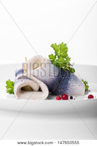 Rollmops (rolled marinated herring) with marinated cucumber salt pepper and parsley closeup