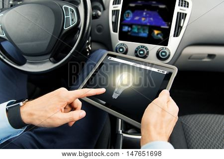 transport, business trip, technology, innovation and people concept - close up of male hands holding tablet pc computer with light bulb icon on screen in car