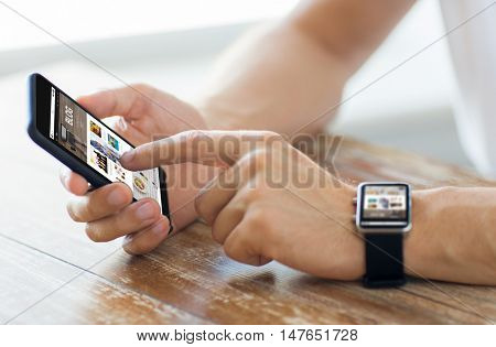 business, technology, blogging and people concept - close up of male hands on wooden table holding smartphone and wearing smart watch with internet blog page on screen