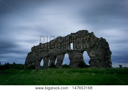 Remnants of the old castle and wind tangled grass in the evening light. Architecture in Laiuse Estonia Europe.