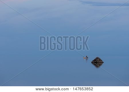 Boat fisherman and sunlight on the coast. Man fishing in evening blue sky reflection on water. Beach in summer. Seaside natural environment. Shore in island Nature Reserve in Estonia Europe