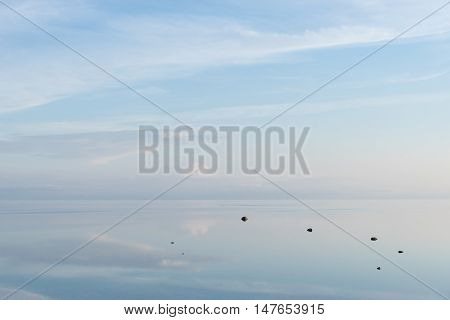 Evening sunlight on coast pink clouds blue sky reflection on water. Beach in summer. Seaside natural environment. Shore in Osmussaar Island Nature Reserve in Estonia National Park in Europe
