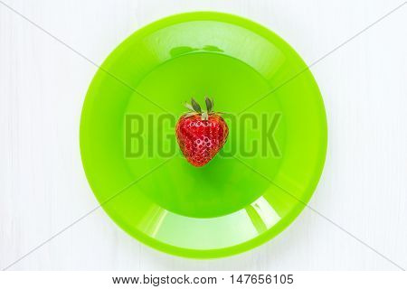 Fresh single strawberry in green plate on the white wooden table