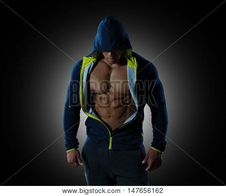 Creative muscle man, abdominal on a black background with illumination behind