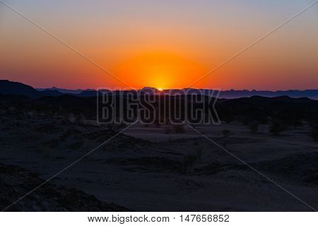 Colorful Sunset Over The Namib Desert, Namibia, Africa. Mountains, Dunes And Acacia Trees Silhouette