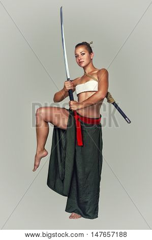 Young flexible girl in the image of the Japanese warrior sword on a light background.