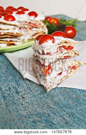 zucchini cake with tomato and parsley on a blue wooden background