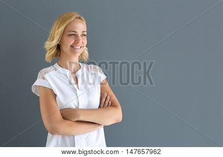 Satisfied smiling blonde woman looking aside