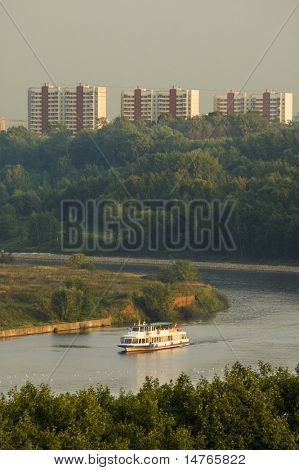 Boat on a river in city in light of sunset