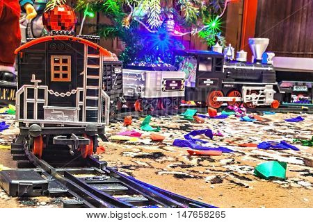 Christmas toy railroad near a Christmas tree with lights.
