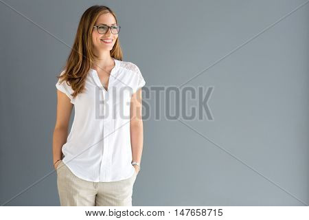 Smiling brunette wearing glasses looking asid