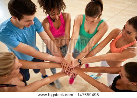 Young fitness group with hands over each other