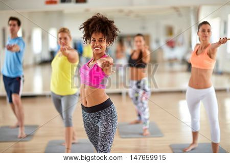 Attractive women in fitness center keep body in condition with exercises