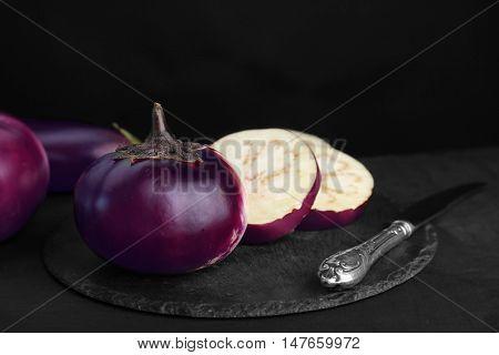 Round sliced aubergines on black background