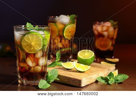 Kitchen board with cuba libre cocktails, lime and mint on wooden table