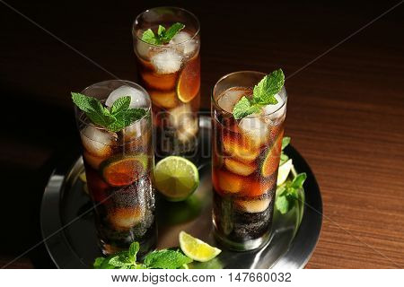 Metal tray with cuba libre cocktails, lime and mint on wooden table