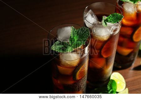 Cuba Libre cocktails with lime and mint on dark background