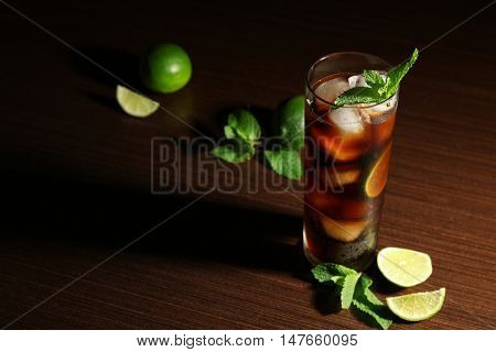 Cuba Libre cocktail with lime and mint on dark background