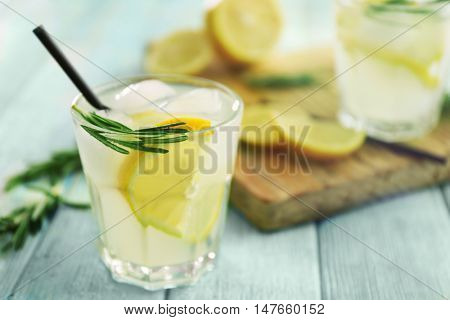 Cold fresh cocktail with lemon on wooden background