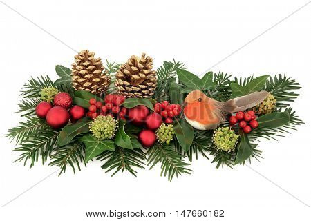 Christmas decoration with red bauble and robin decorations, holly, ivy, gold pine cones and winter greenery over white background.