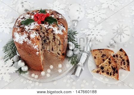 Italian chocolate panettone christmas cake and slice with holly berries, silver and white bauble and snowflake decorations.