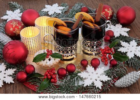 Christmas party food and drink with mulled wine and mince pie, bauble decorations, holly and snow covered fir.