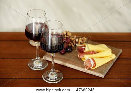Glasses with red wine and tasty snacks on wooden table
