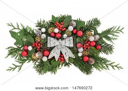 Christmas decoration with silver glitter bow, bauble decoartions, holly and red berries, snow covered pine cones, and winter greenery over white background.