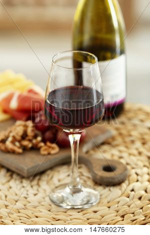 Glass with red wine and tasty snacks on a board on wicker mat