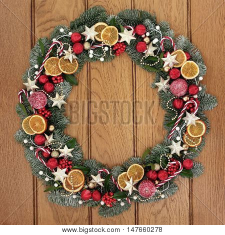 Christmas wreath with dried fruit, candy canes, gold star and red baubles, holly, mistletoe, pine cones and snow covered blue spruce fir over oak wood front door background.