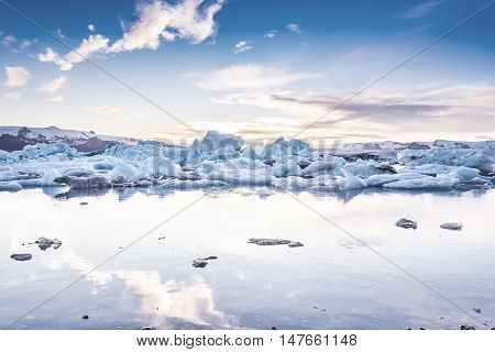 Scenic view of icebergs in Jokulsarlon glacier lagoon Iceland at sunset selective focus cool vintage style effect