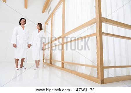No stress today. Beautiful couple wearing in white terry robes and holding hands while walking along hall of spa center