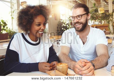 Beautiful interracial couple drinking coffee at cafeteria handsome bearded Caucasian man in glasses telling something funny to his cute African American girlfriend both wearing casual clothes