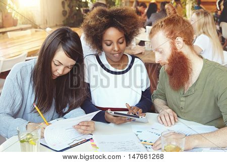 Redhead Caucasian male and his Asian and African female college mates preparing for classes of Economics sitting at cafe. Dark-skinned student girl showing something to her bearded friend on tablet