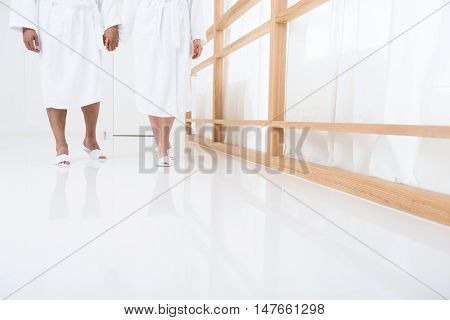 Chilling at spa. Cropped shot of couple walking together and holding hands in spa salon, wearing white terry bathrobes and slippers