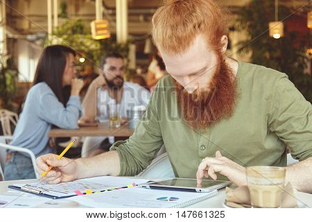Young Trendy Entrepreneur With Long Red Hair And Beard Working On Prospective Business Plan Sitting