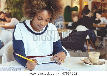 Portrait Of Young Dark-skinned Woman In Casual Clothes Sitting At University Canteen Doing Home Assi