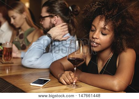 Sad Pensive Down Hearted Dark-skinned Woman With Glass Of Red Wine At Bar Counter During New Year Ce